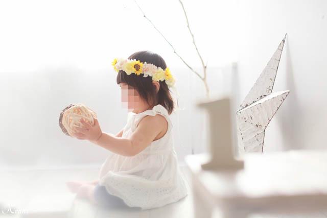 1歳のお誕生日にひまわりとバラの花冠を身に着けた可愛い女の子1